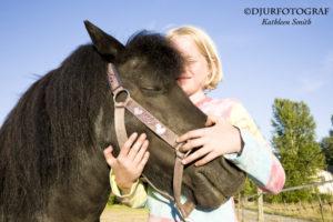 Flicka som kramar sin ponny